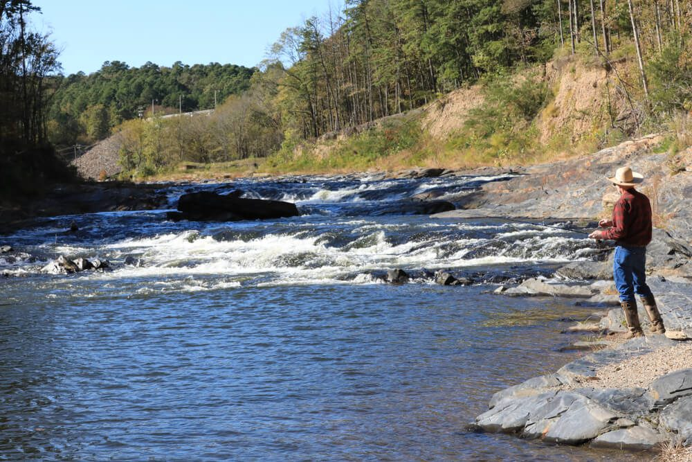 A man pariticipating in one of Beavers Bend State Parks' most popular activities, fishing.
